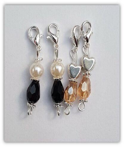 fyra stickmarkörer i svart, vitt och ljusbrunt med kräftklolås