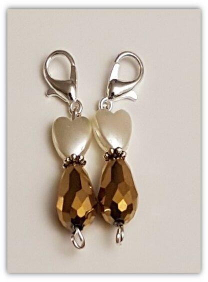 två guldbruna stickmarkörer med kräftklolås