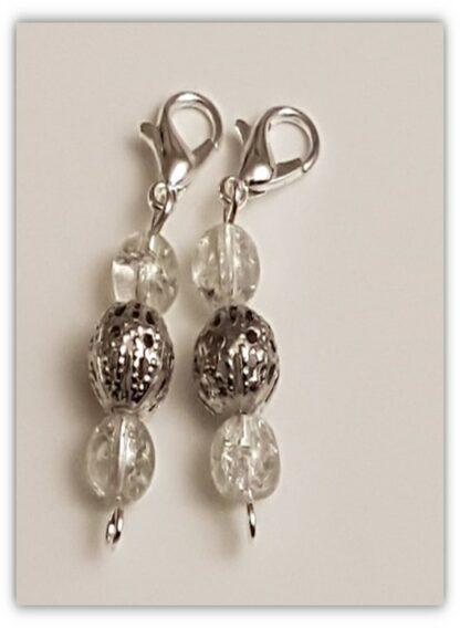 två stickmarkörer i silverfärgade och genomskinliga pärlor och kräftkloknäppning
