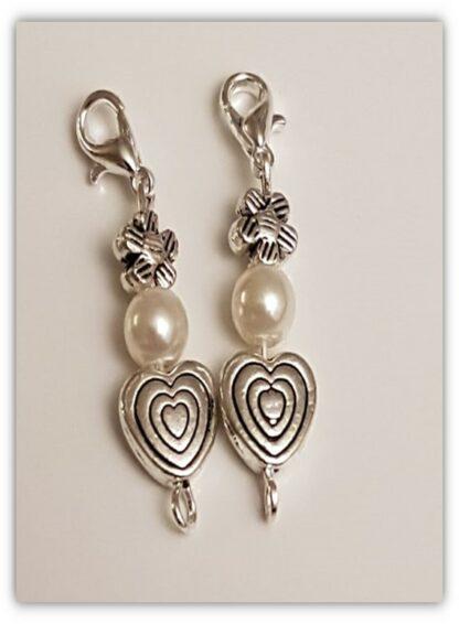 två stickmarkörer med vita pärlor och hjärtan och blomma i silverfärg med kräftklolås