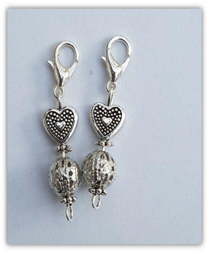 två silvriga stickmarkörer med hjärta och krätfklolås